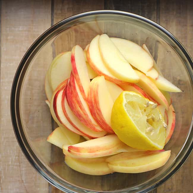 A glass bowl with honey crisp apple slices and a 1/2 lemon on top.