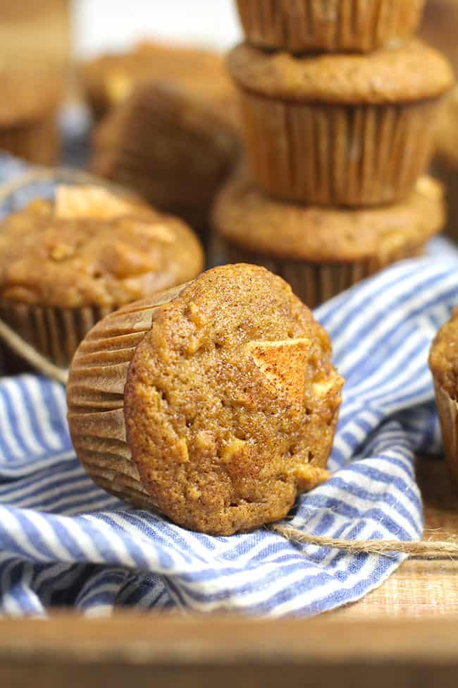 Several applesauce cinnamon muffins, with a closeup on one on its side.