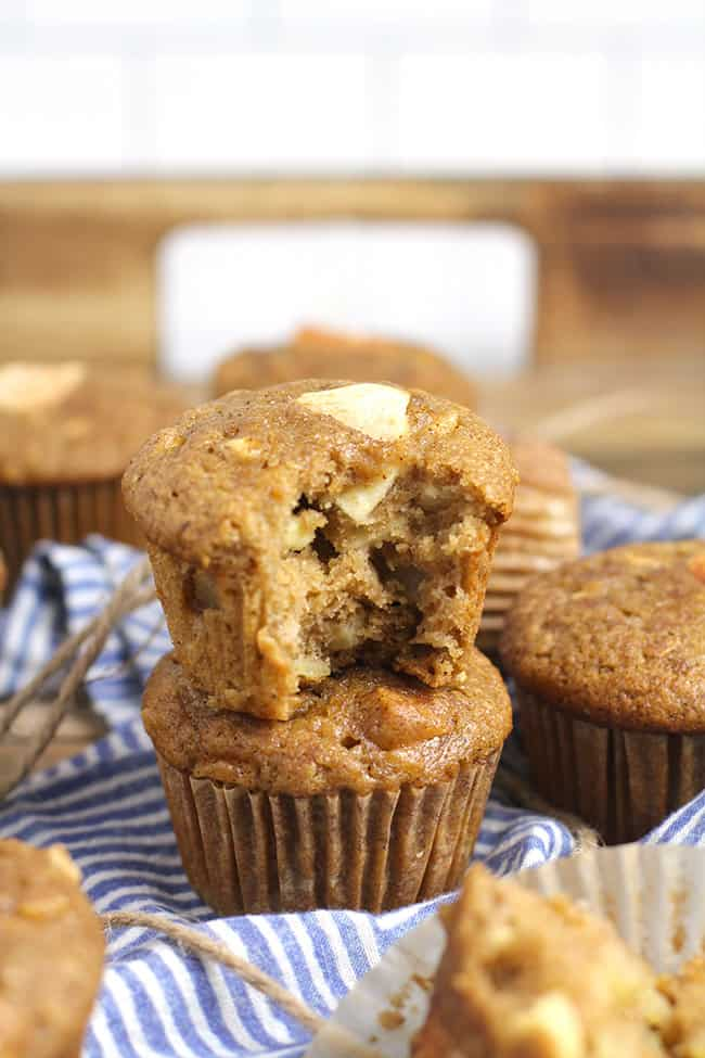 Two stacked apple muffins with a bite out of the top one.