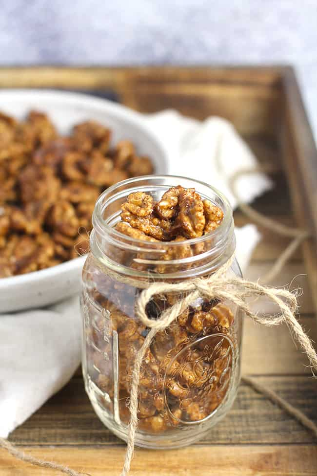 A jar of candied walnuts with a bowl in the background.