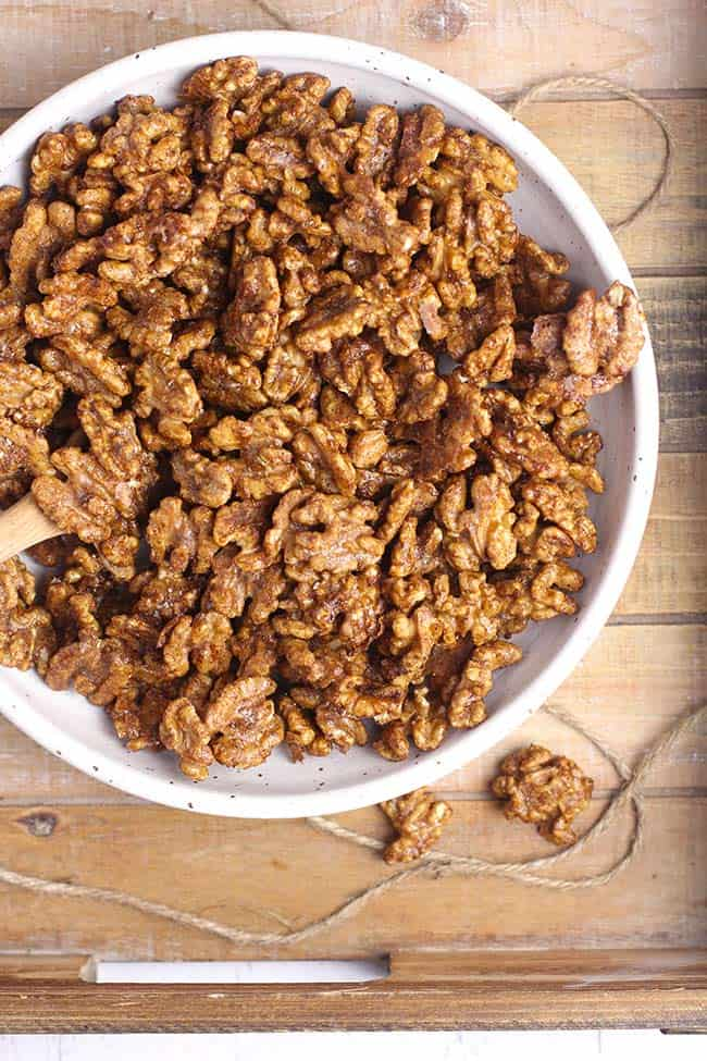 Overhead shot of the candied walnuts in a white bowl on a wooden tray.