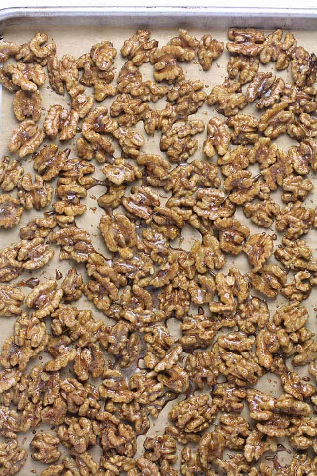 A baking sheet lined with parchment paper with candied walnuts.
