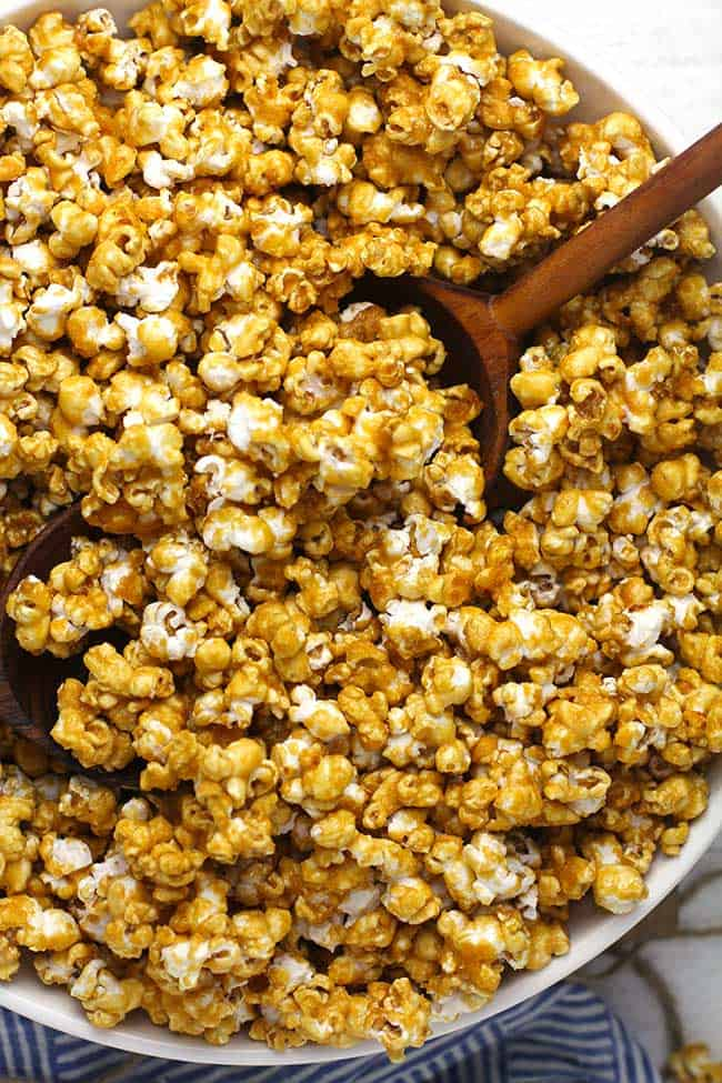 A large white bowl of caramel popcorn, with some wooden spoons.