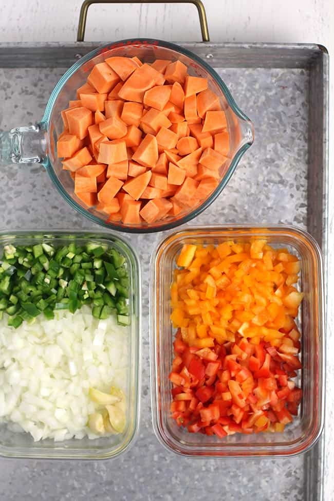 A gray tray with all the chopped veggies in dishes, ready to use in the chili.