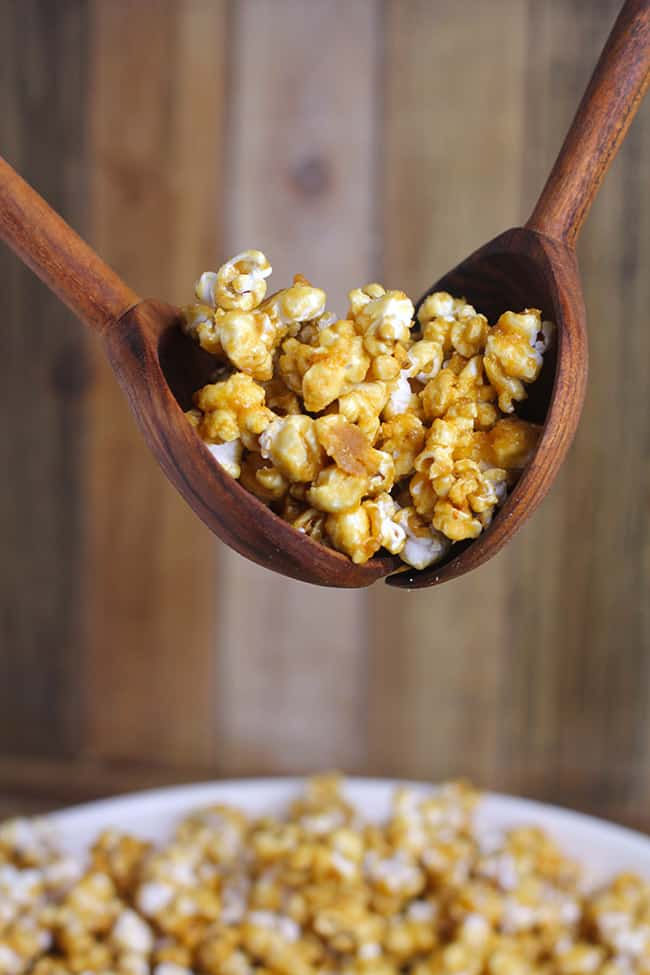 Two spoons lifting up some caramel popcorn over a large bowl.