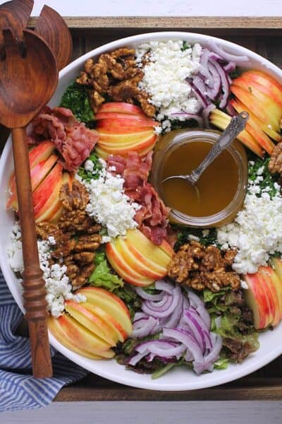 Overhead shot of a large loaded fall harvest salad with balsamic dressing.