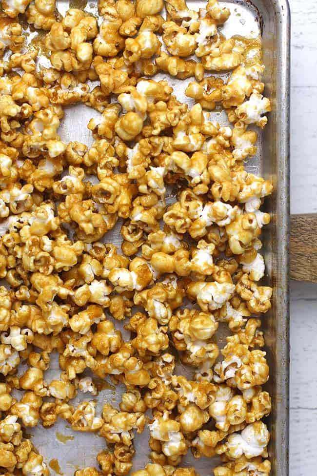 A sheet pan with the caramel popcorn spread out.