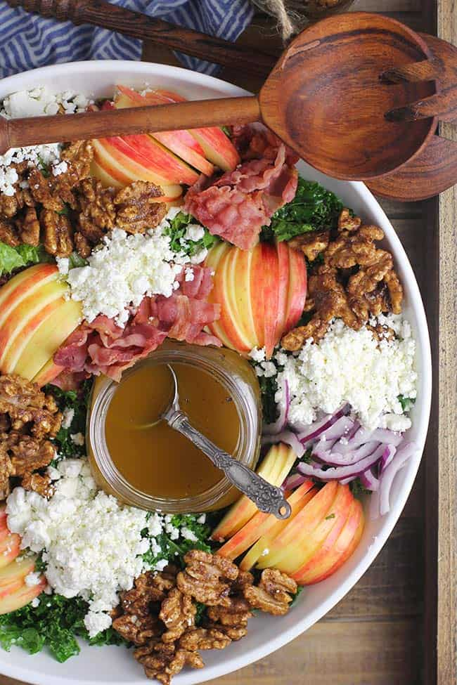 A large bowl of loaded harvest salad, with wooden spoons.
