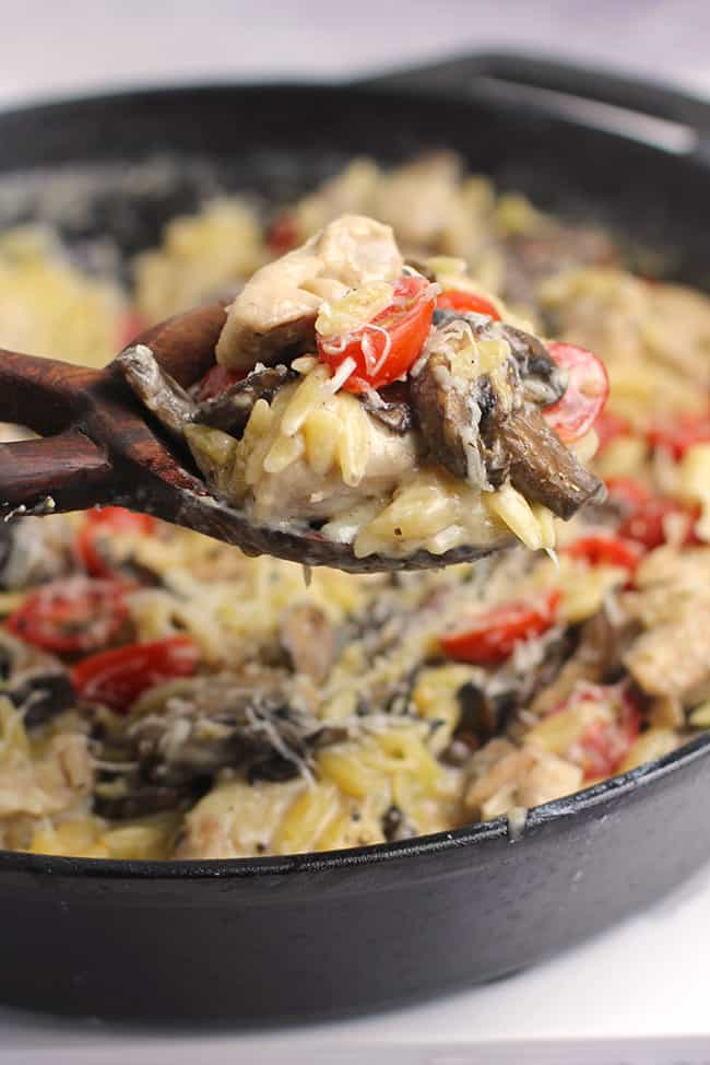 A spoonful of parmesan chicken orzo being lifted out of a skillet.