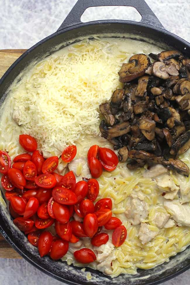 The finished parmesan chicken orzo skillet with the parmesan, mushrooms, and tomatoes on top in sections.