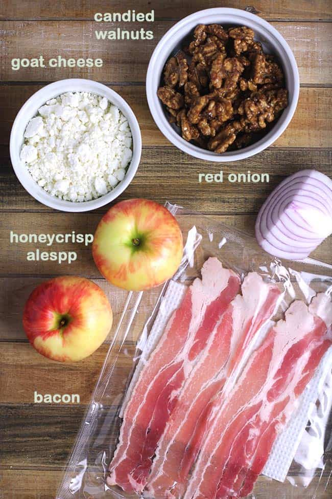 A wooden tray with all the ingredients for a loaded fall harvest salad.