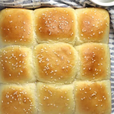 Overhead shot of a square loaf of soft brioche diner rolls, on a blue and white napkin.