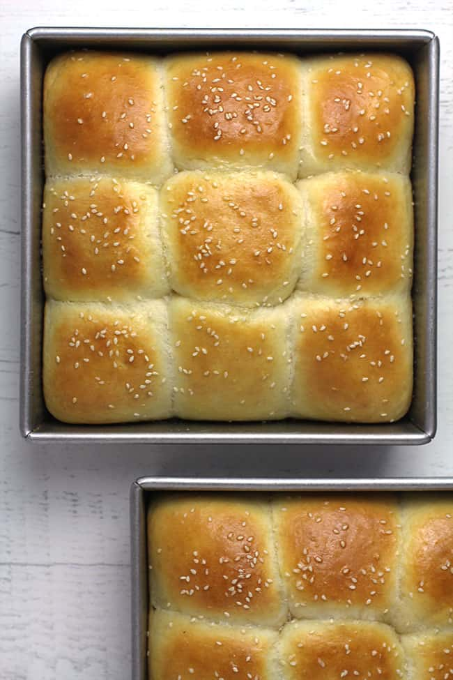 Two pans of just baked brioche dinner rolls, with sesame seeds on top.