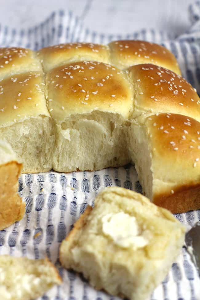 Side shot of a loaf of brioche dinner rolls with two removed, and one with butter.