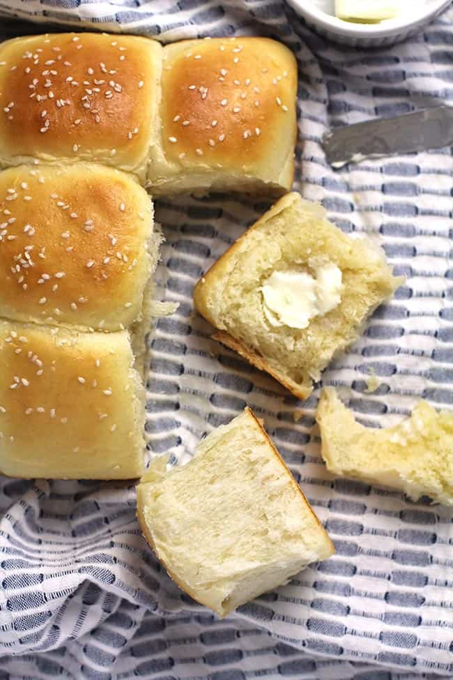 Some brioche dinner rolls, one pulled apart, and one with a pat of butter.