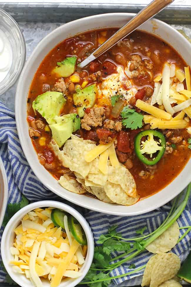 Overhead view of a bowl of turkey taco soup with all of the toppings.