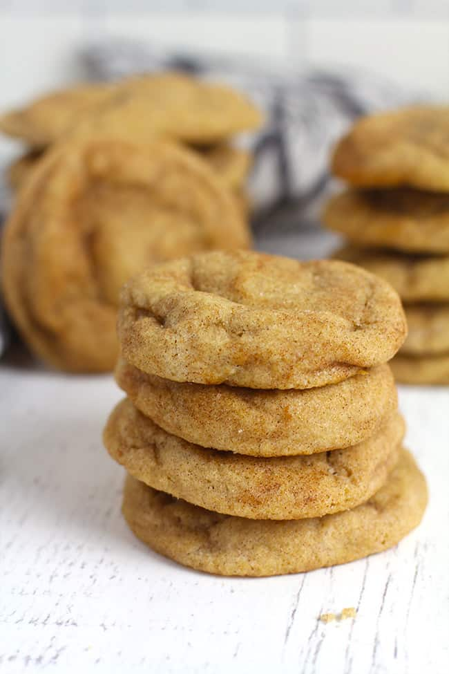 A stack of three snickerdoodle cookies, with more cookies in the background.