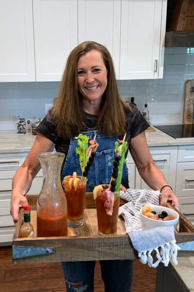 Me, holding a wooden tray of Bloody Marys and a partial carafe.