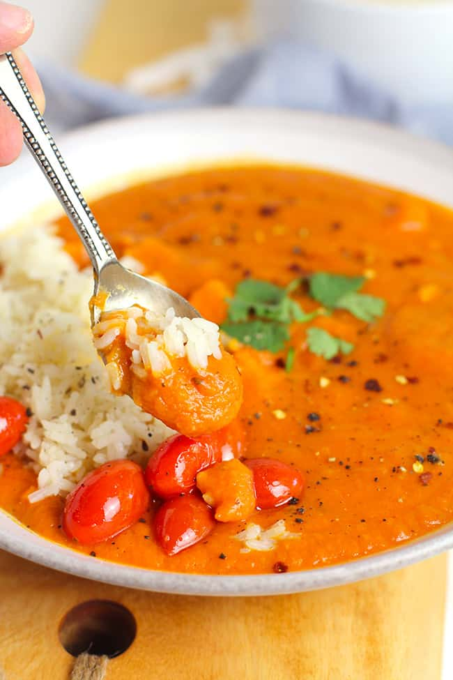 A spoonful of the sweet potato curry soup, overtop the bowl.
