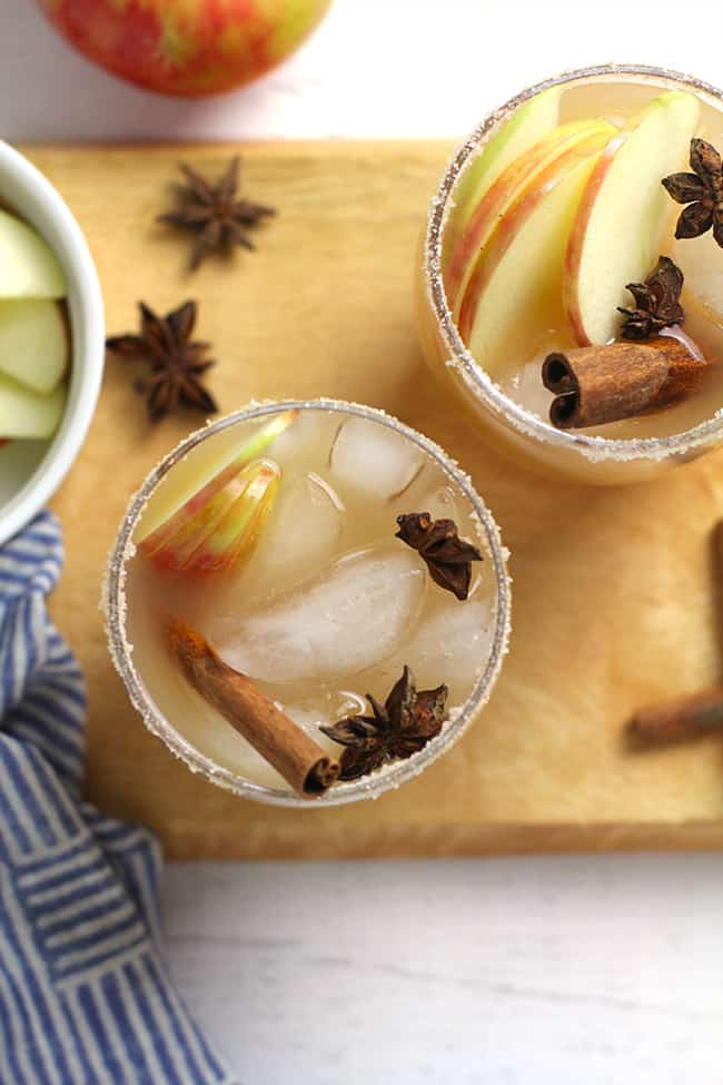 Overhead shot of two glasses of apple cider margaritas on a wooden board.