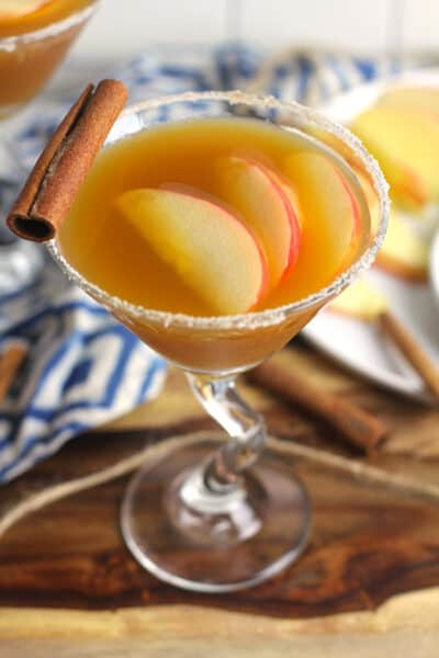 Side overhead shot of a apple cider martini, with apple slices inside and a cinnamon stick.