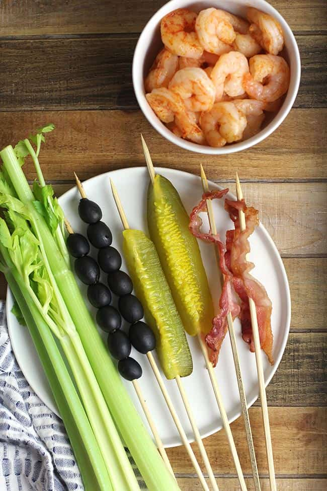 A tray with garnishes - celery, olives, pickles, bacon, and shrimp.