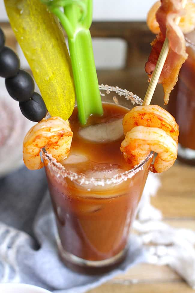 Overhead shot of a Bloody Mary cocktail, with garnishes.