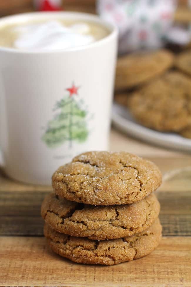 Three gingersnap cookies stacked up on a wooden tray with a Christmas cup of coffee.