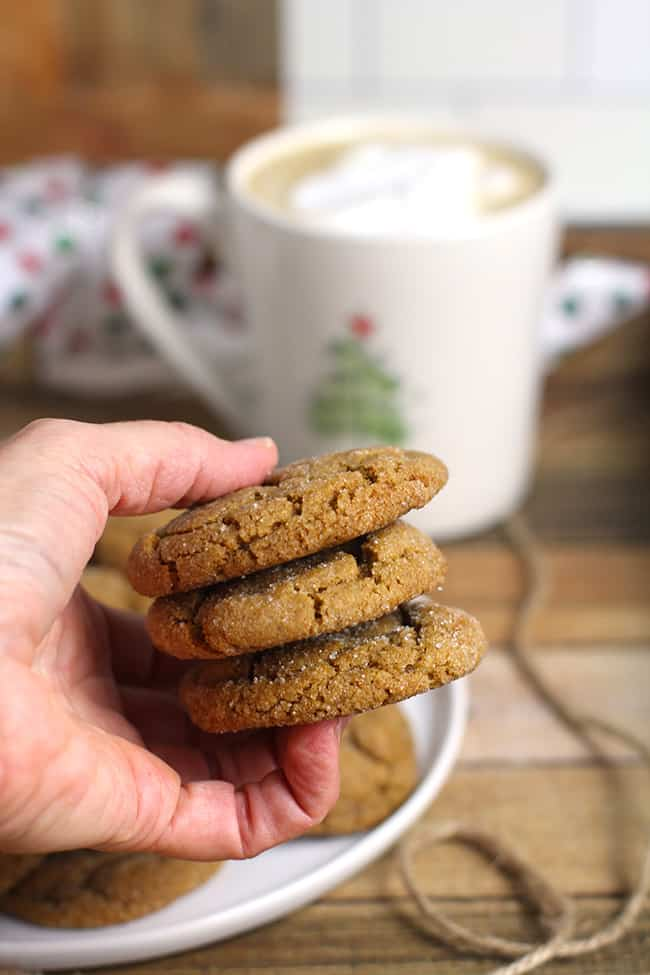 My hand holding three gingersnap cookies above a cup of coffee.