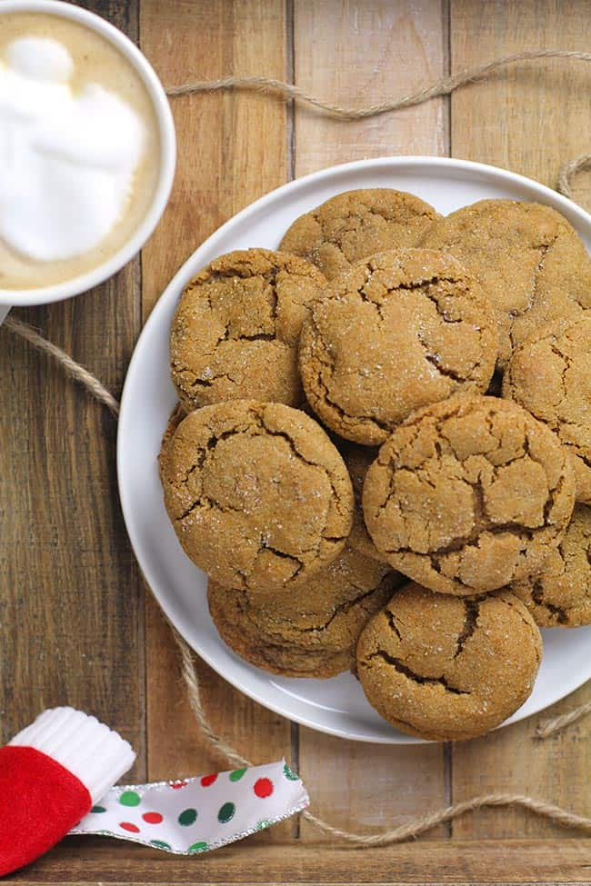 A plate of gingersnap cookies on a wooden tray with a cup of coffee.