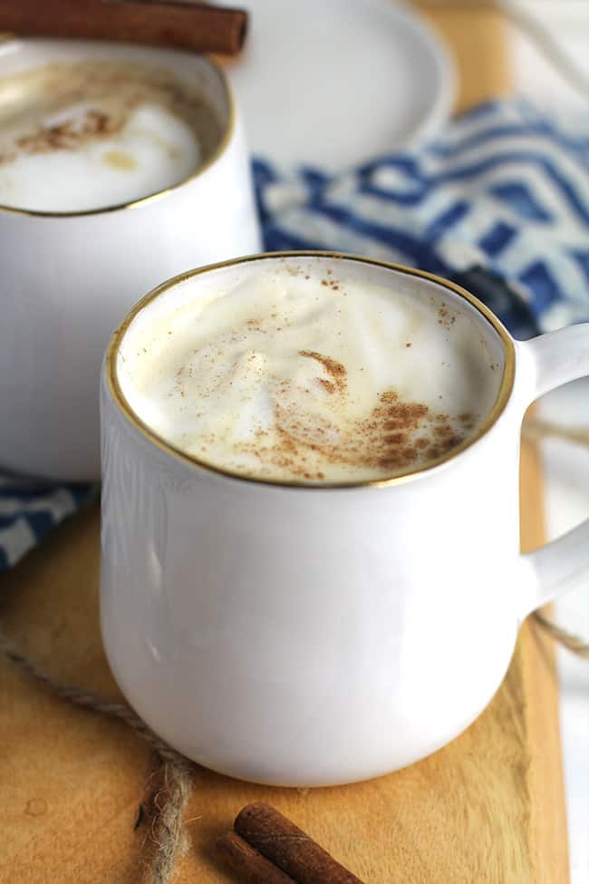 Side shot of a mug of homemade pumpkin latte with cinnamon and a milk froth.