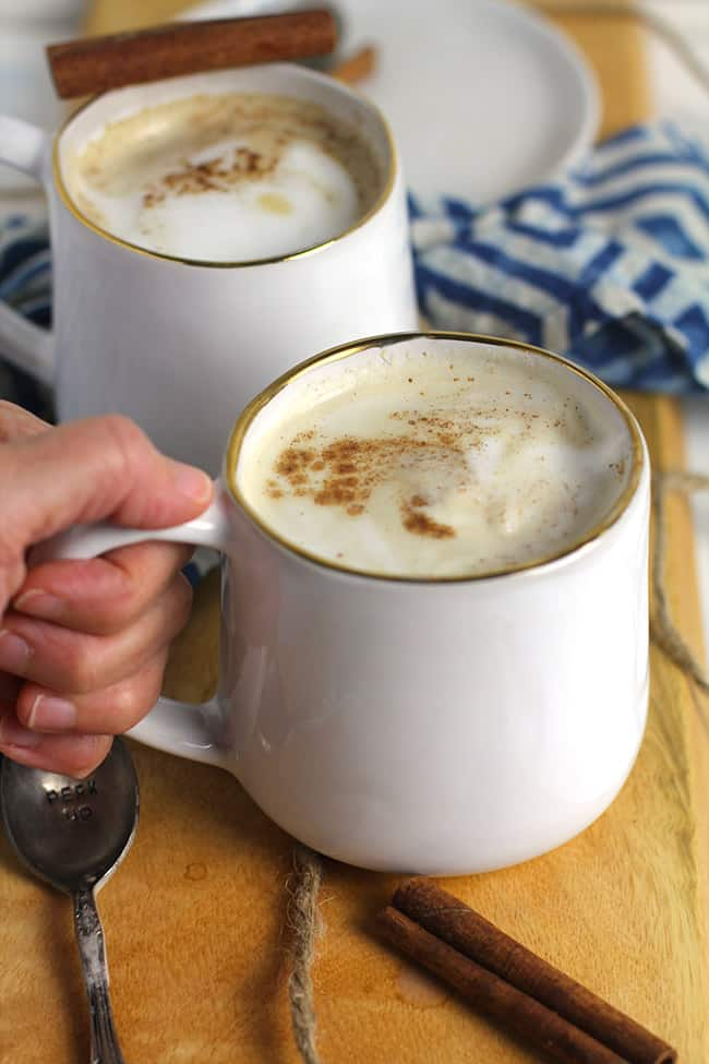 My hand holding a mug of homemade pumpkin spice latte, with a mug in the background.