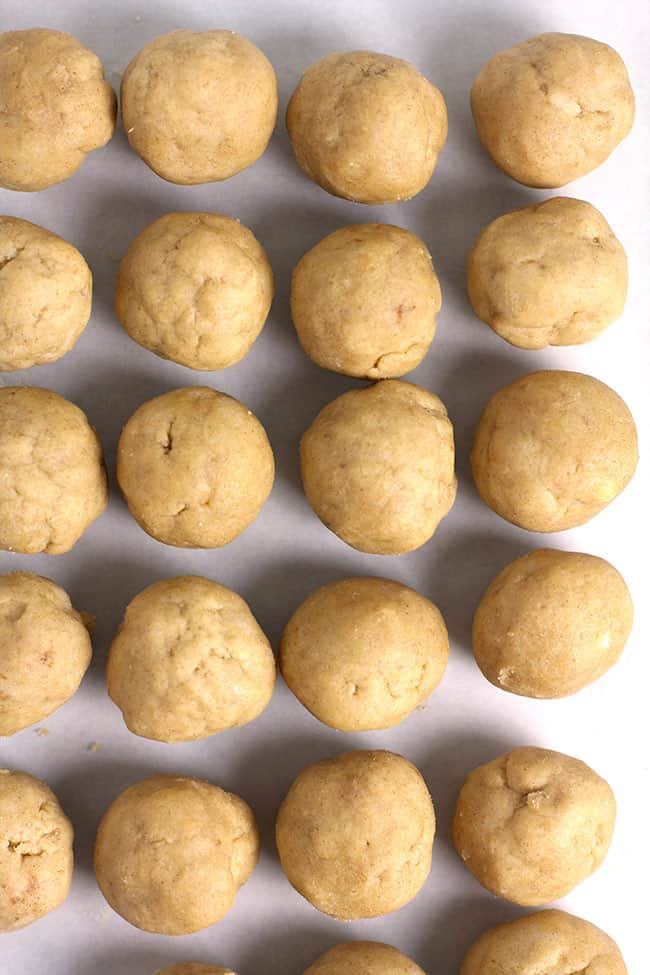 Overhead shot of snickerdoodle cookie balls on white parchment.