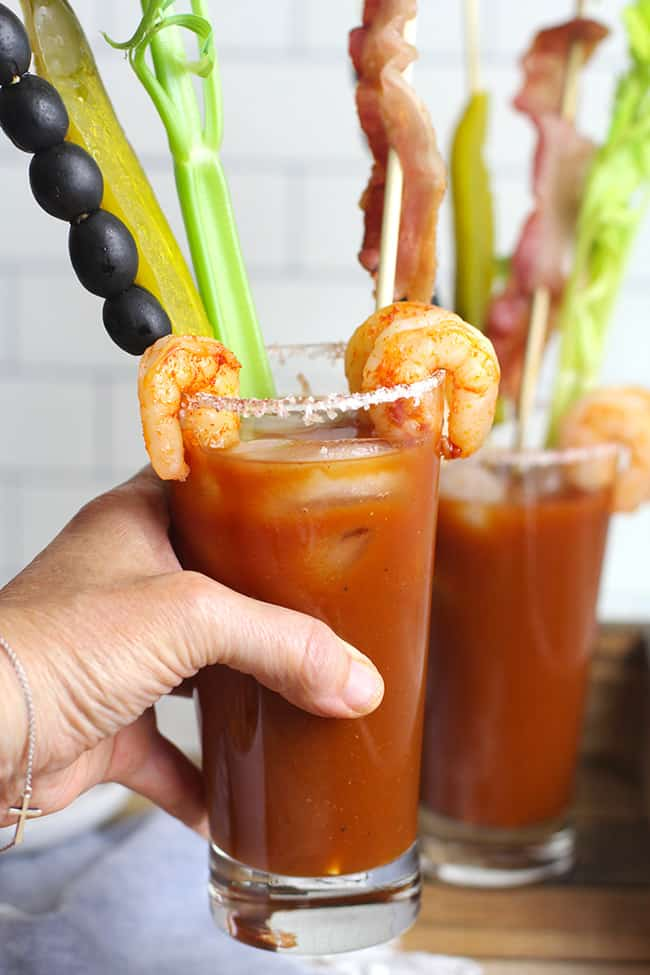 My hand holding a Bloody Mary cocktail with garnishes.