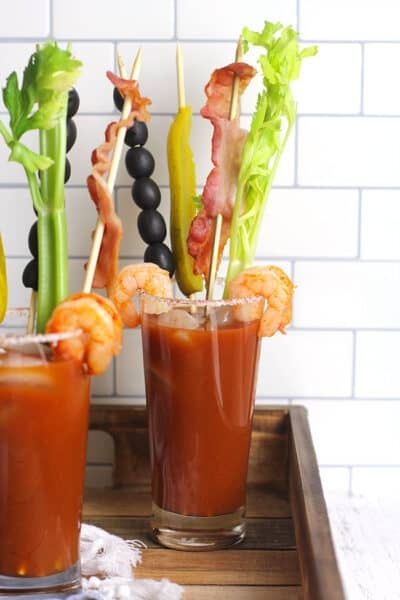 Side shot of two glasses of spicy Bloody Mary, on a wooden tray.