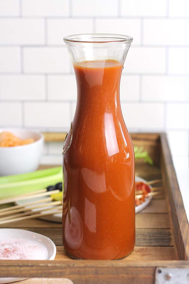 A carafe of Bloody Mary mix, on a wooden tray with the garnishes.