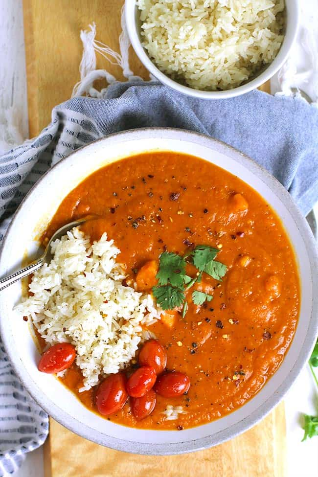 Overhead shot of a bowl of sweet potato curry soup with rice and tomatoes, on a wooden board.