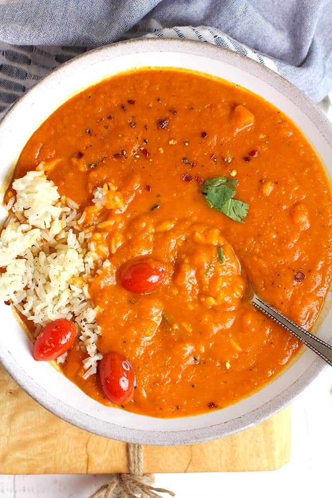 A bowl of sweet potato curry soup, with white rice and cherry tomatoes.