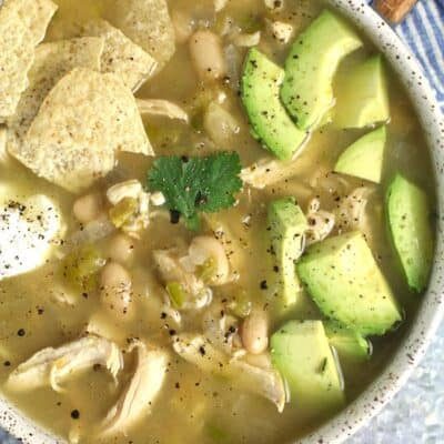 Closeup shot of a white speckled bowl of green chili chicken soup, with chips, avocado, and sour cream.