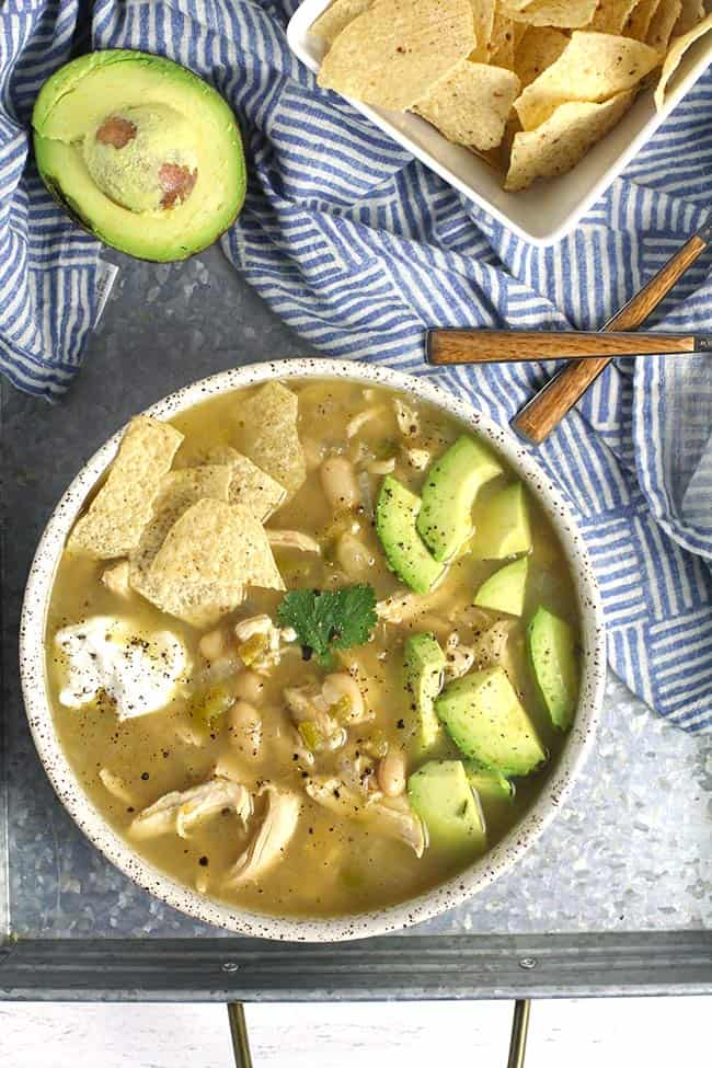 A bowl of green chili chicken soup on a tray with avocado, and a bowl of chips.