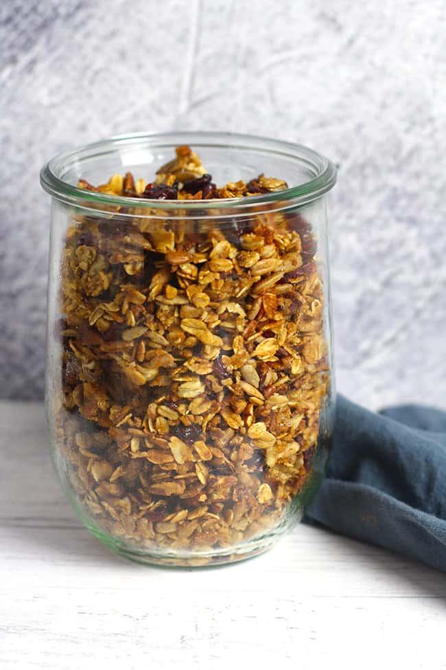 Side shot of a large jar of cranberry nut granola.