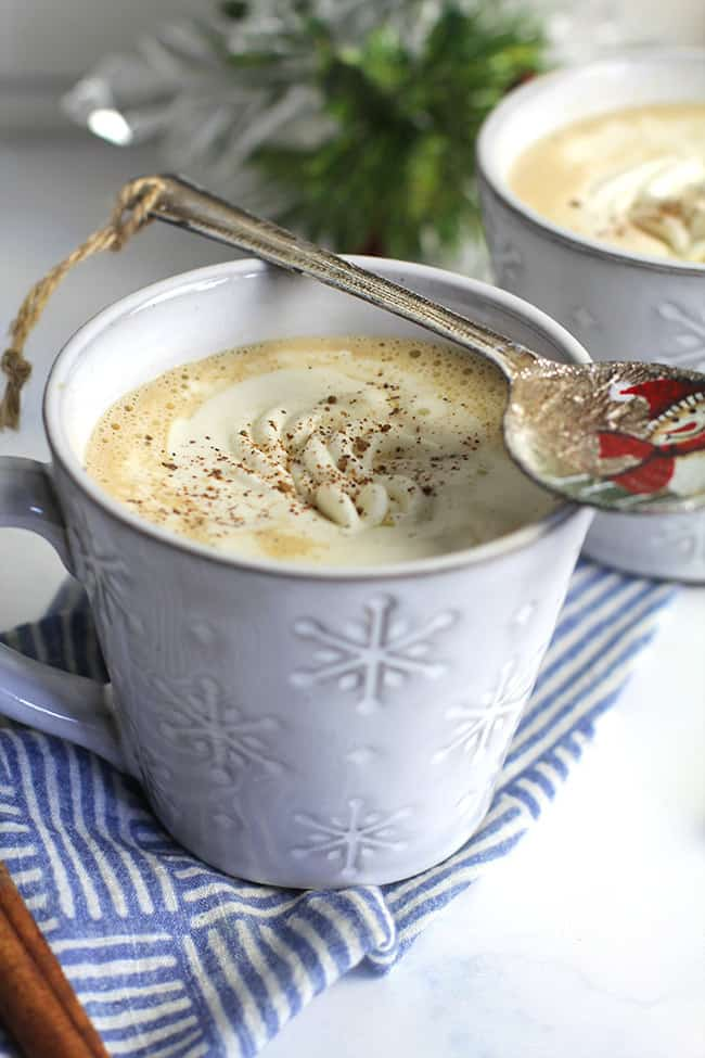 Side shot of two mugs of homemade eggnog latte, with a Christmas spoon on top.