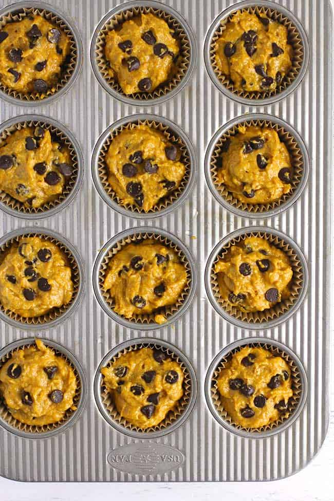 A muffin pan filled with pumpkin muffin batter, topped with chocolate chips.