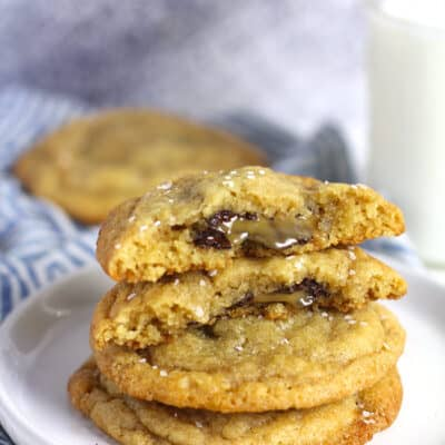 A stack of salted caramel stuffed cookies, with two half cookies, showing the caramel and chocolate ooze.