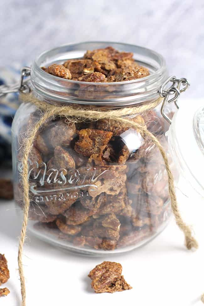 Side shot of a large mason jar of candied pecans.