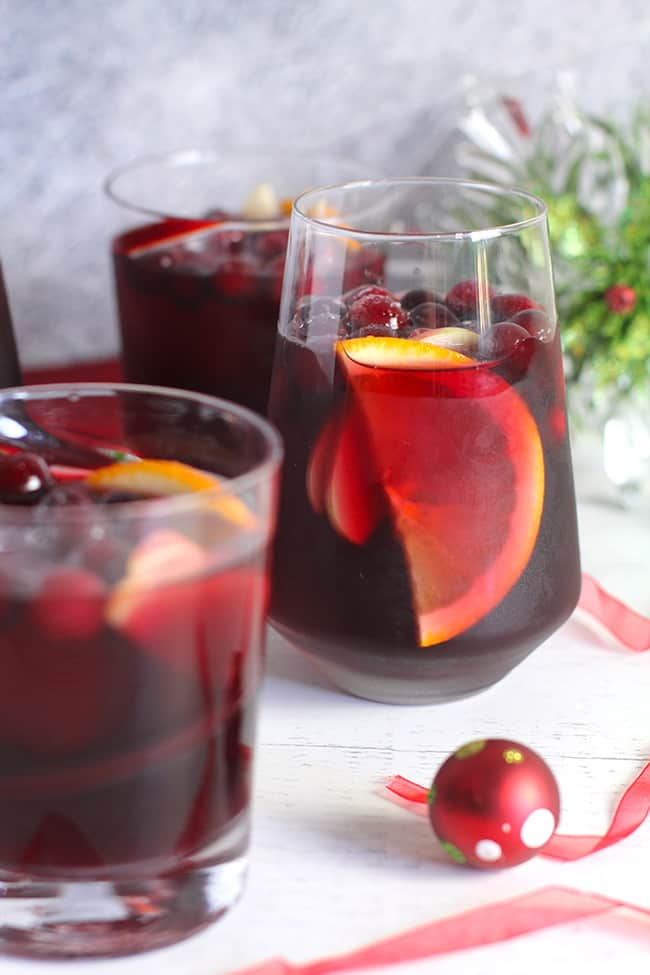 Side view of several glasses of cranberry sangria.