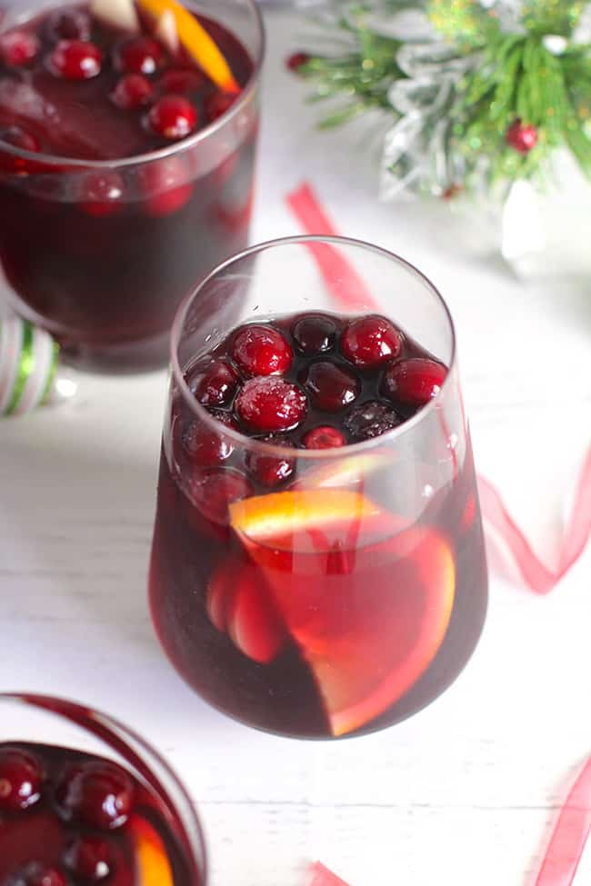 Overhead shot of two glasses of cranberry sangria, on a white surface.