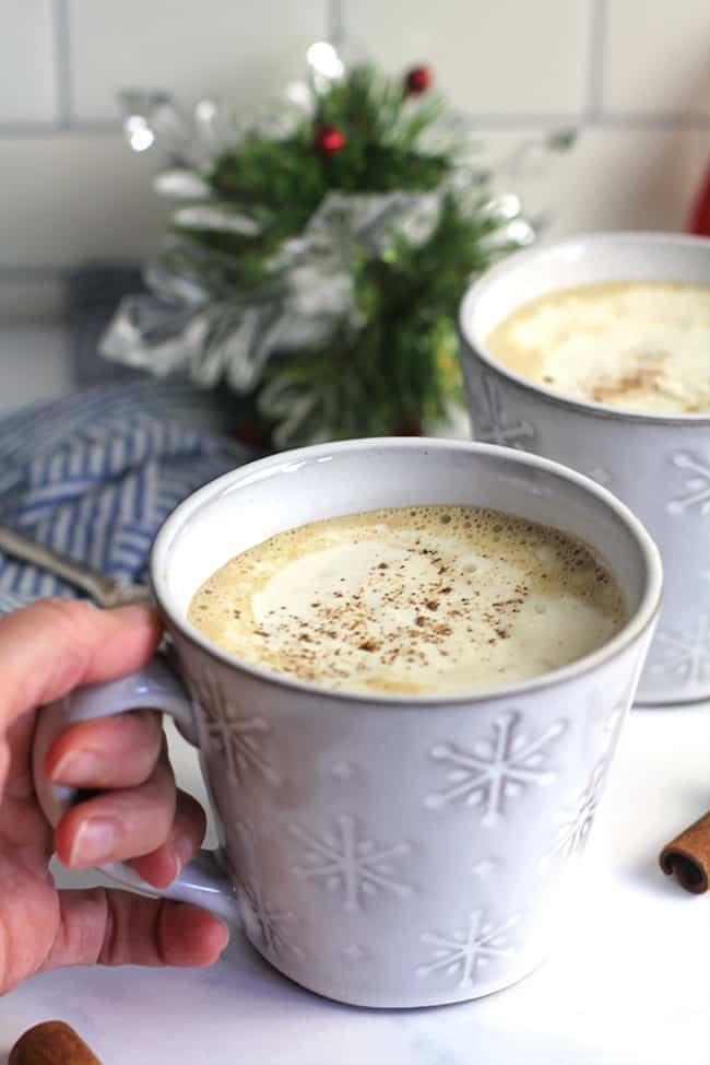 My hand on a mug of eggnog latte, with another one in the background.