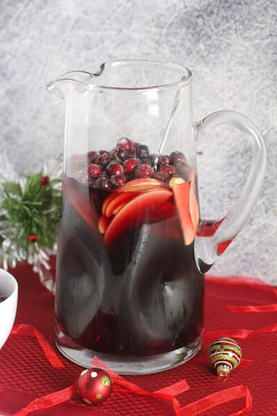 A large pitcher of cranberry sangria recipe, on a red placemat with ornaments around it.
