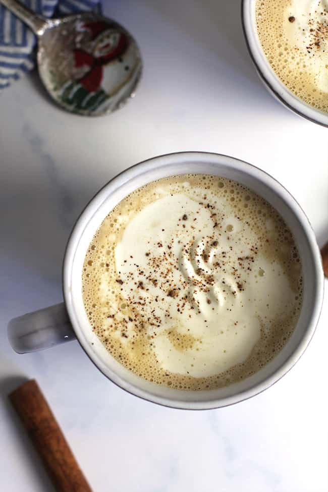 Overhead shot of a mug of eggnog latte, with a cinnamon stick.